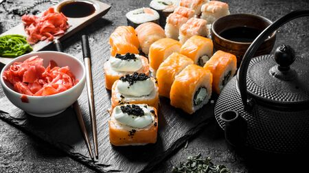 Sushi rolls with salmon and shrimp on a stone stand. On black rustic background