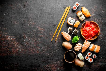 Pieces of delicious Japanese sushi and rolls with soy sauce. On dark rustic background Stockfoto