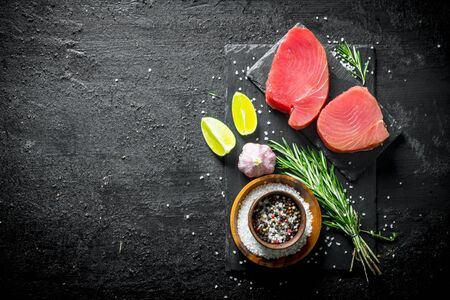 Pieces of fresh raw tuna on a stone Board with spices, garlic, lime and rosemary. On black rustic background