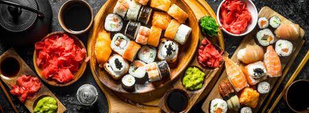 Set traditional Japanese sushi rolls on cutting boards. On rustic background