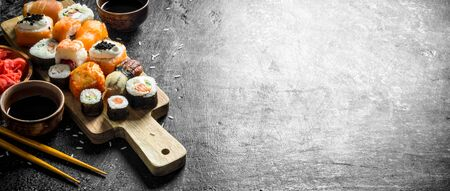 Japanese seafood sushi on cutting Board. On dark rustic background