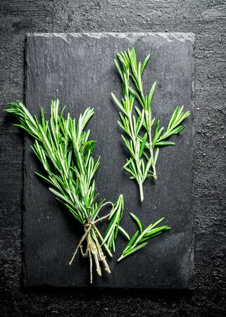 Rosemary on a stone board. On black rustic background