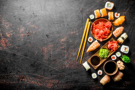 Set of traditional Japanese sushi and rolls with marinated ginger and soy sauce. On dark rustic background