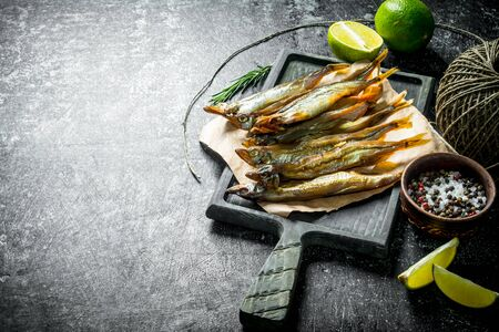 Smoked fish on paper with lime slices, spices and old twine. On dark rustic background