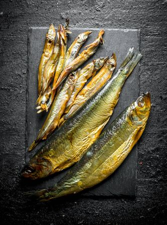 Different smoked fish on a stone Board. On black rustic background