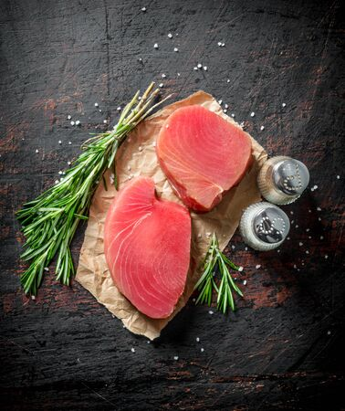 Pieces of fresh raw tuna with rosemary and spices. On dark rustic background