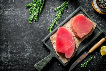 Raw tuna fillet on a cutting Board with spices and rosemary. On dark rustic background Stok Fotoğraf