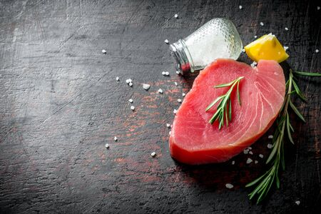 Piece of uncooked tuna steak with spices, rosemary and lemon. On dark rustic background Stok Fotoğraf