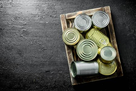 Assortment of different kinds of tin cans with canned food on tray. On black rustic background 스톡 콘텐츠