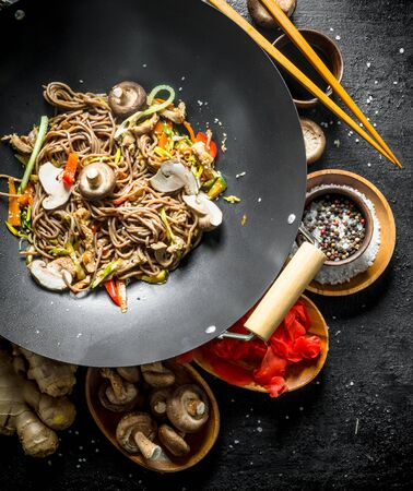 Delicious Asian soba noodles with spices, mushrooms and ginger. On black rustic background