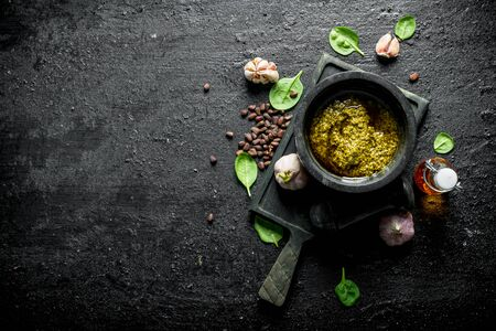 Pesto sauce with pine nuts, Basil and olive oil. On black rustic background 写真素材