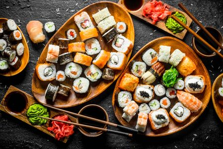 Set of traditional Japanese food sushi with soy sauce and ginger. On black rustic background