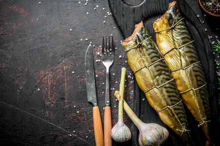Delicious smoked mackerel on a cutting Board. On dark rustic background