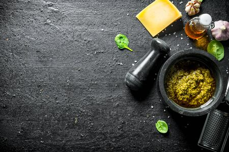 Pesto sauce with olive oil, Parmesan and garlic. On black rustic background