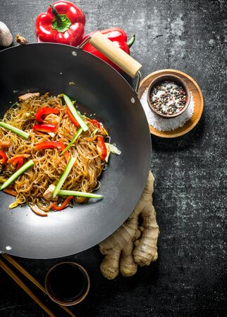 Chinese cellophane noodles in a frying pan wok with ginger, spices and vegetables. On dark rustic background Stockfoto