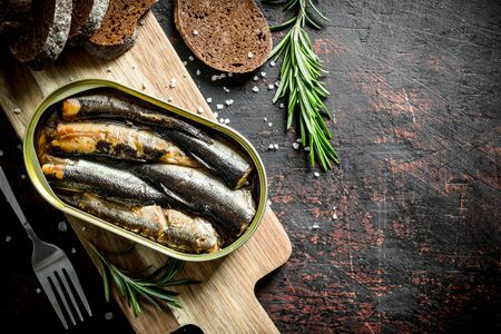 Sprats with rosemary and sliced bread. On dark rustic background