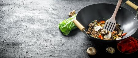 Fragrant soba noodles in a wok pan. On black rustic background Stockfoto