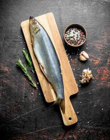 Salted herring on a cutting Board with garlic, spices and rosemary. On dark rustic background