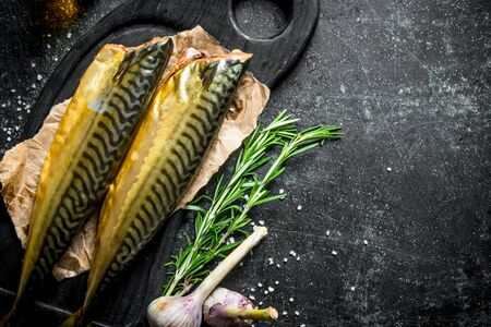Smoked mackerel on a cutting Board with rosemary and garlic. On dark rustic background Stok Fotoğraf