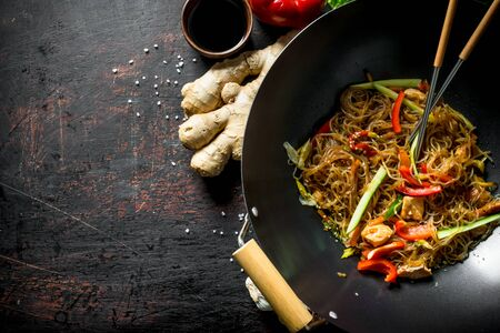 Freshly cooked Chinese noodles wok funchoza with salmon, vegetables and sauce. On dark rustic background