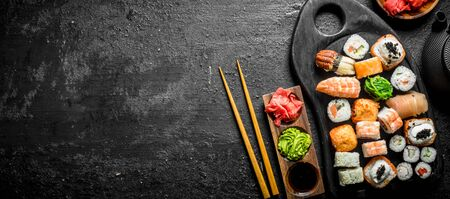 Set of different kinds of sushi rolls with salmon, shrimp and vegetables. On black rustic background