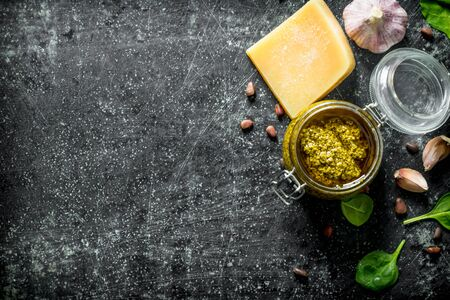 Pesto sauce in a jar with Basil, garlic cloves and Parmesan. On dark rustic background 写真素材