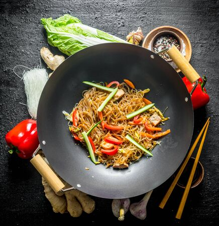 Chinese wok. Ingredients for cooking funchoza with vegetables. On black rustic background