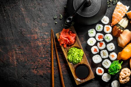 Different types of Japanese sushi, rolls and maki with sauce, wasabi and green tea in a teapot. On dark rustic background