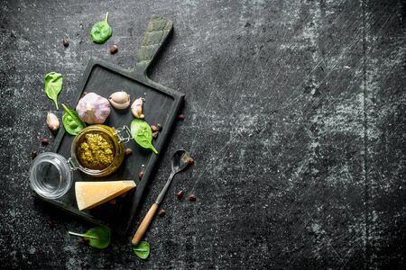 Pesto sauce on a cutting Board with Parmesan, Basil and garlic. On dark rustic background
