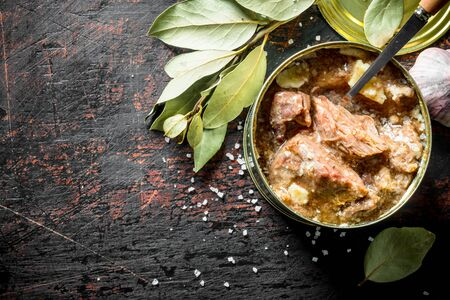 Open a tin of canned meat. On dark rustic background