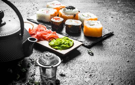 Pieces of delicious Japanese sushi rolls with green tea and sauces. On black rustic background Stockfoto