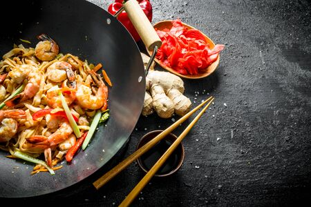 Wok Udon noodles with ginger, soy sauce and bell pepper. On black rustic background