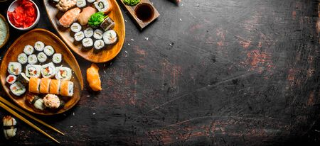 Assorted variety of sushi, rolls and Maki on the plates. On dark rustic background Stockfoto