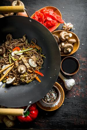 Chinese soba noodles in wok pan with ginger, spices, soy sauce, garlic and vegetables. On dark rustic background