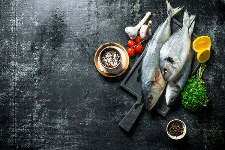 Fresh fish on a cutting Board with herbs, spices, tomatoes and garlic. On dark rustic background 写真素材