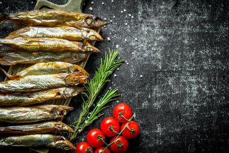 Delicious smoked fish with rosemary and tomatoes on a branch. On dark rustic background