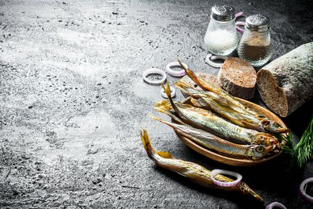 Smoked fish with sliced bread, spices and onion rings. On black rustic background