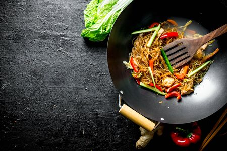 Fragrant Chinese funchoza with fresh vegetables. On rustic background Stockfoto