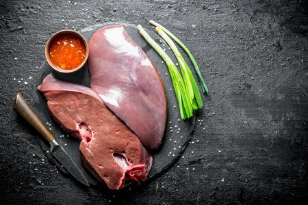 Pieces of raw liver on a stone Board with sauce and onions. On black rustic background 스톡 콘텐츠