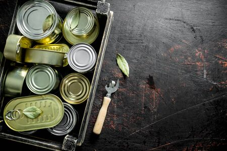 Closed cans of canned food in a box with a opener. On dark rustic background