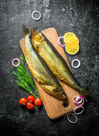 Smoked fish on a wooden cutting Board with tomatoes, dill and lemon slices. On dark rustic background