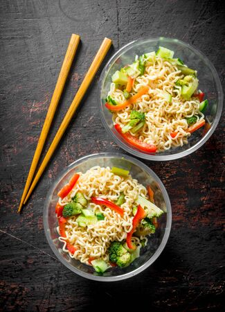 Instant noodles in glass bowls with vegetables. On dark rustic background