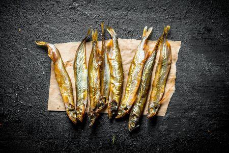 Smoked fish sprat on paper. On black rustic background