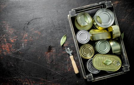 Canned food in closed cans in a box. On dark rustic background Banco de Imagens