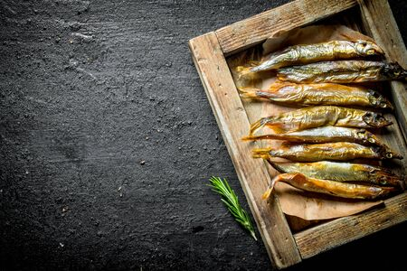Smoked fish on the tray with the rosemary. On black rustic background
