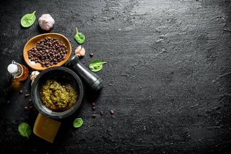 Pesto sauce with pine nuts, garlic and Basil. On black rustic background