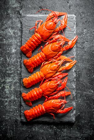 Cooked crayfish on a stone Board. On dark rustic background