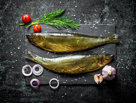 Smoked fish on a stone Board with dill, tomatoes, garlic and onions. On dark rustic background