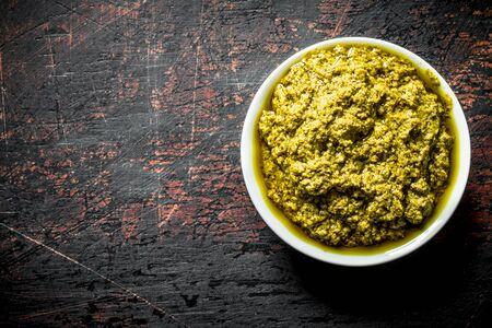 Pesto sauce in bowl. On dark rustic background