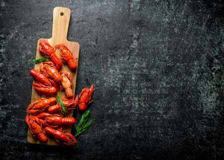 Boiled crayfish on a wooden cutting Board with dill. On dark rustic background